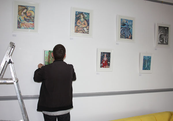 Hanging pictures for the open house.